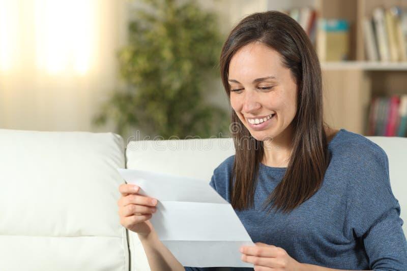 Lycklig kvinna som hemma l?ser ett brev p? en soffa royaltyfri bild