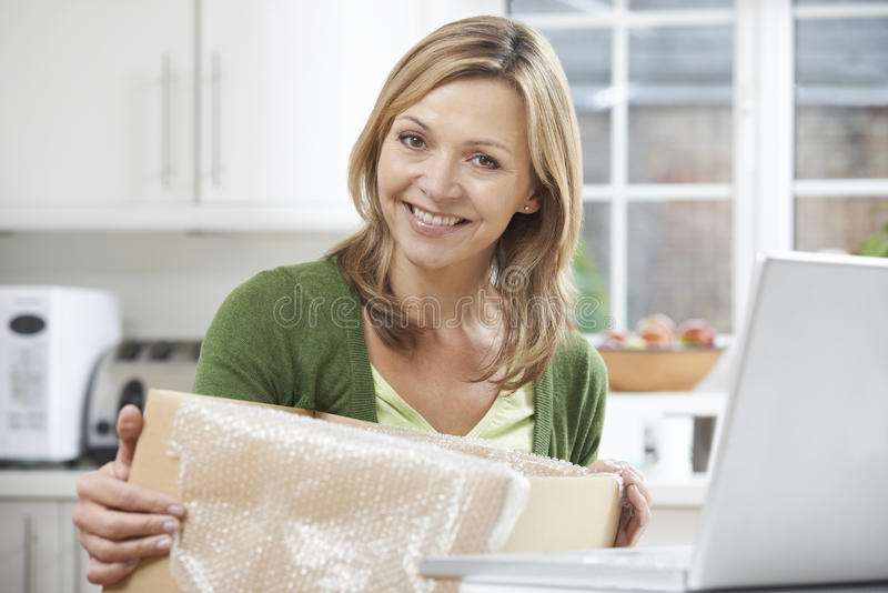 Lycklig kvinna som hemma packar upp online-köpet arkivfoton