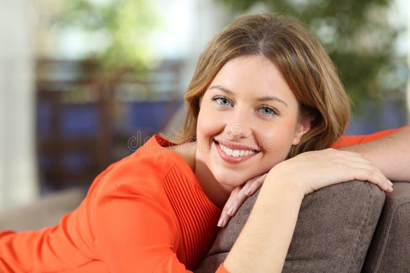 Lycklig kvinna som hemma poserar att se kameran royaltyfria foton