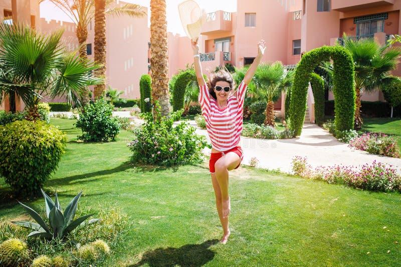 Lycklig kvinna som hoppar över gräset på hotellet royaltyfri foto