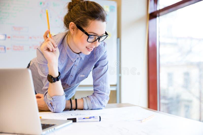 Lycklig kvinna som i regeringsställning arbetar med ritningen nära fönstret arkivfoton