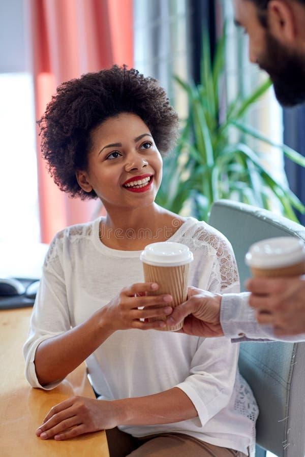 Lycklig kvinna som i regeringsställning tar kaffe från man royaltyfria bilder
