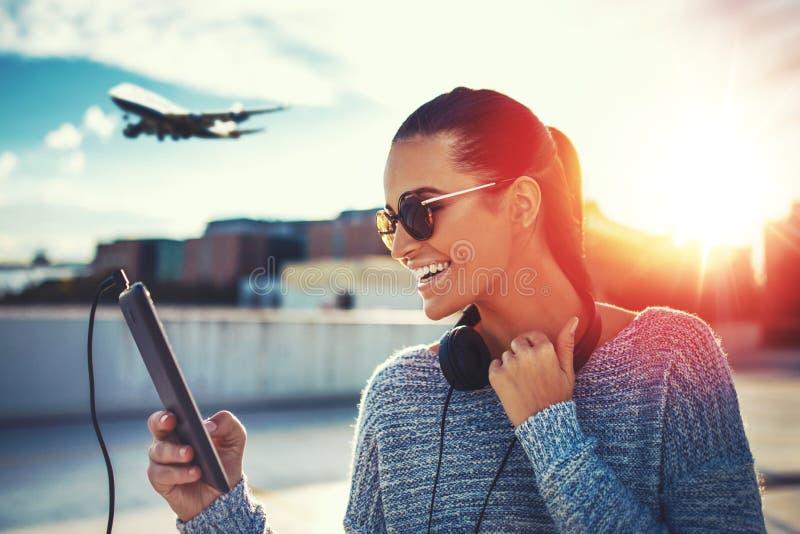 Lycklig kvinna som inhandlar flygbiljetten vid minnestavlan royaltyfri fotografi