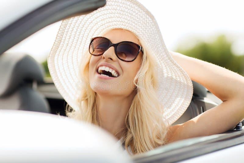 Lycklig kvinna som kör i cabrioletbil royaltyfria bilder