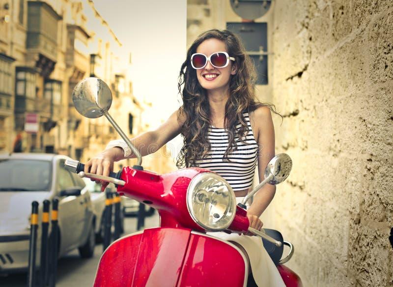 Lycklig kvinna som kör moppad royaltyfri fotografi