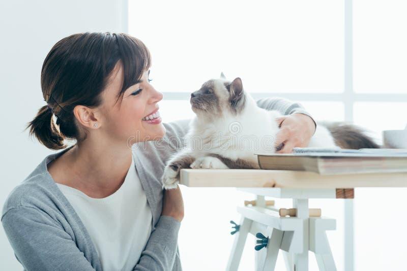 Lycklig kvinna som kelar hennes katt royaltyfri foto