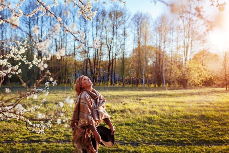 Lycklig kvinna som kopplar av i vårträdgård Hög kvinna som går i fält Dam som tycker om liv arkivfoto