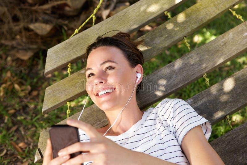 Lycklig kvinna som kopplar av på hängmattan som lyssnar till musik arkivfoto