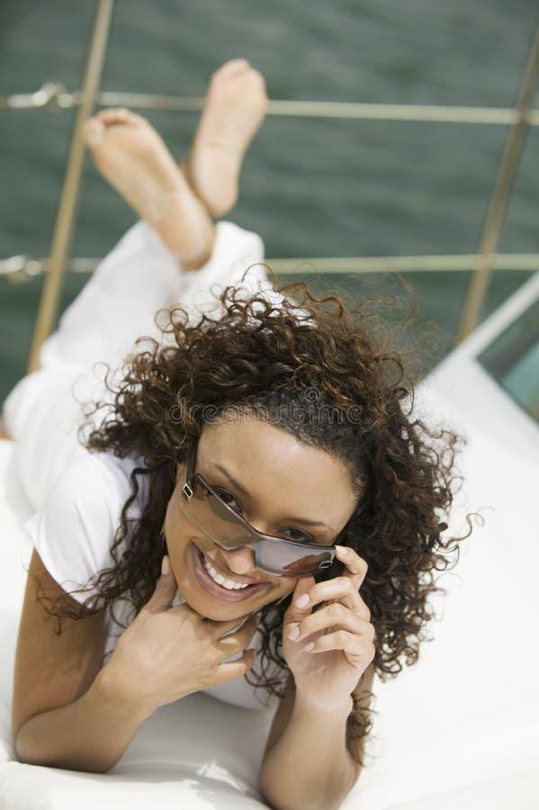 Lycklig kvinna som kopplar av på yachten arkivfoto