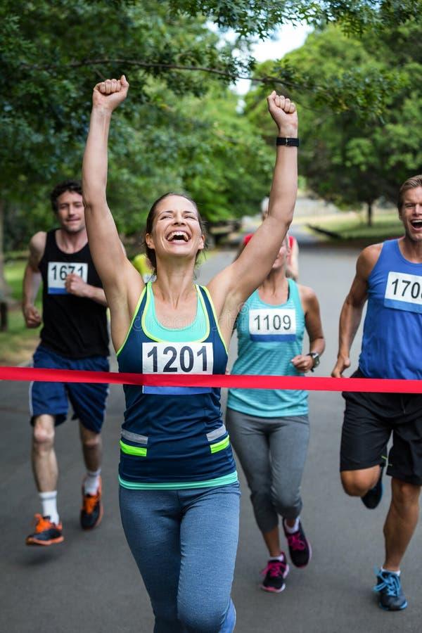Lycklig kvinna som korsar mållinjen royaltyfria foton