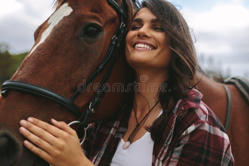 Lycklig kvinna som kramar hennes häst royaltyfri fotografi