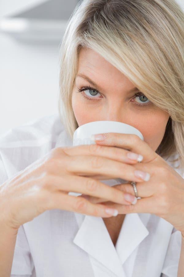 Lycklig kvinna som läppjar kaffe i morgonen fotografering för bildbyråer