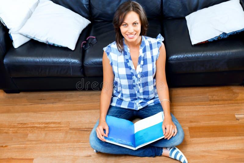 Lycklig kvinna som läser en bok på golvet arkivfoto
