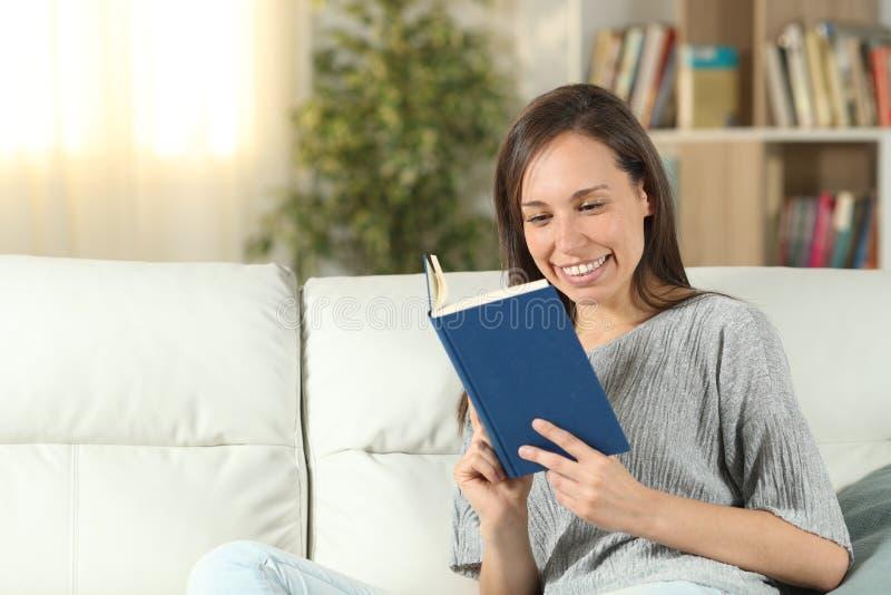 Lycklig kvinna som läser en pappers- bok som sitter på en soffa royaltyfri fotografi