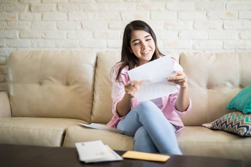 Lycklig kvinna som läser ett brev arkivbilder