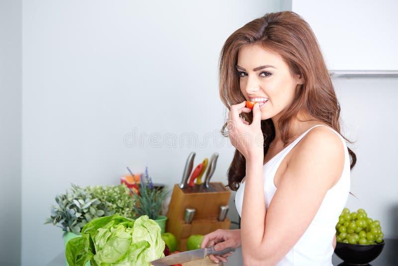 Lycklig kvinna som lagar mat ett mål i köket royaltyfria foton