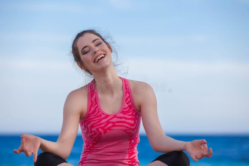 Lycklig kvinna som ler göra yoga royaltyfri fotografi