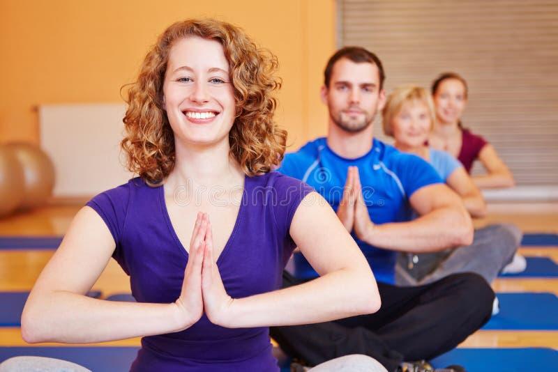 Lycklig kvinna som ler i yogagrupp fotografering för bildbyråer