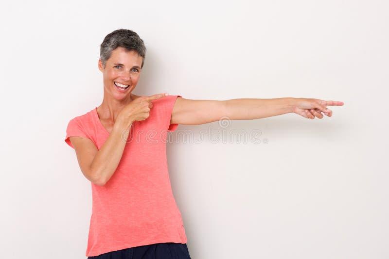 Lycklig kvinna som ler mot vit bakgrund och pekar fingrar royaltyfri fotografi