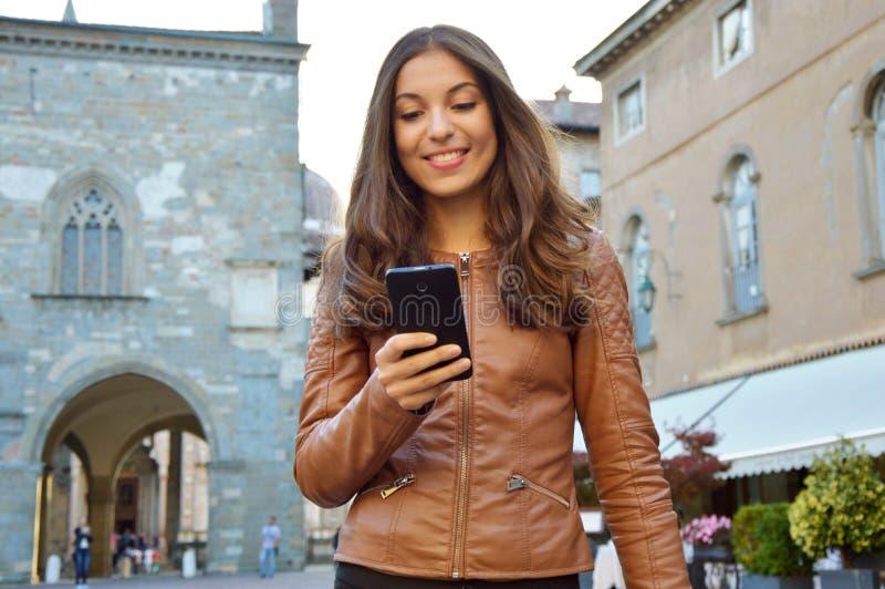 Lycklig kvinna som ler och går i gatan genom att använda en ny app på smartphonen arkivbild