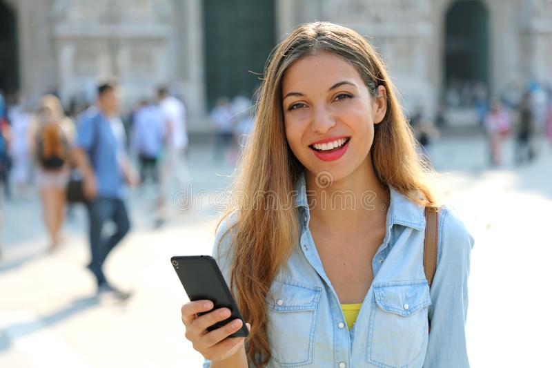 Lycklig kvinna som ler och går i gatan genom att använda en smartphone royaltyfri bild