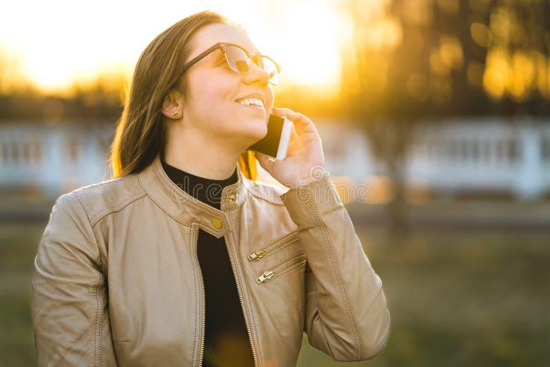 Lycklig kvinna som ler och skrattar, medan tala på telefonen royaltyfri bild