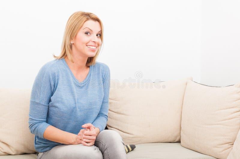 Lycklig kvinna som ler på en soffa eller en soffa royaltyfri bild