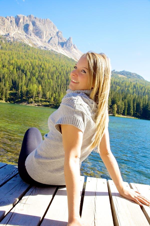 Lycklig kvinna som ler se kameran i semester i berg och sjön arkivbild