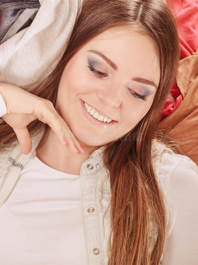 Lycklig kvinna som ligger på kläder Röra och oordning royaltyfri fotografi