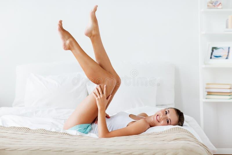 Lycklig kvinna som ligger på säng och hemma trycker på ben royaltyfri bild