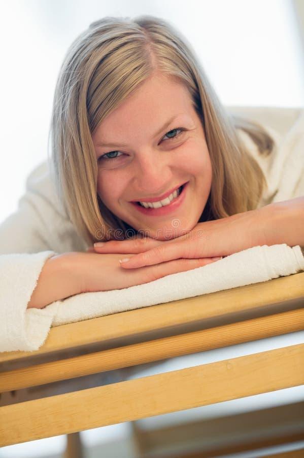 Lycklig kvinna som ligger på säng på brunnsorten arkivbild