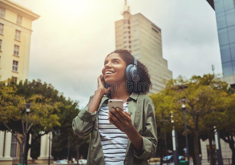 Lycklig kvinna som lyssnar till bärande hörlurar för musik royaltyfri bild
