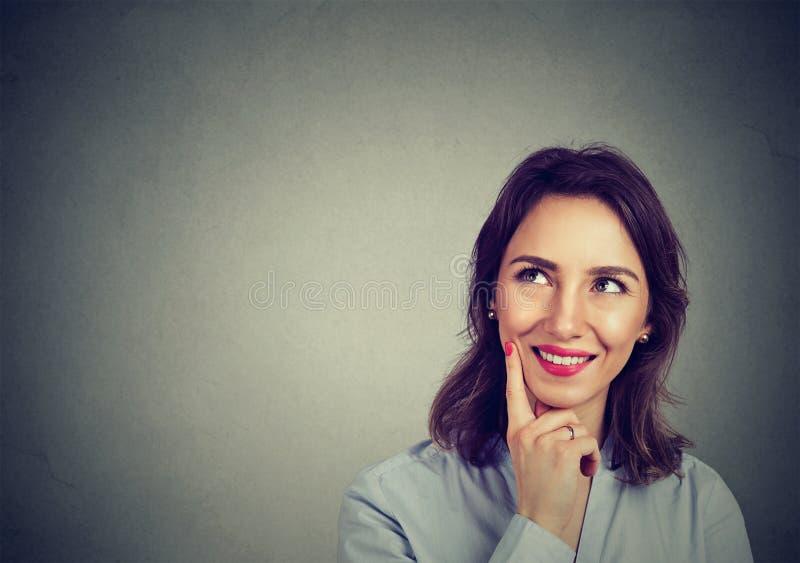 Lycklig kvinna som minns att se upp på att le för sida royaltyfria bilder