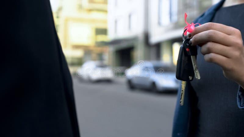Lycklig kvinna som mottar tangenter till den nya bilen från återförsäljarechef, uthyrnings- service royaltyfria bilder