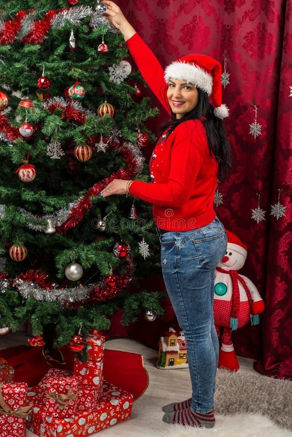 Lycklig kvinna som ordnar Xmas-trädet royaltyfria bilder