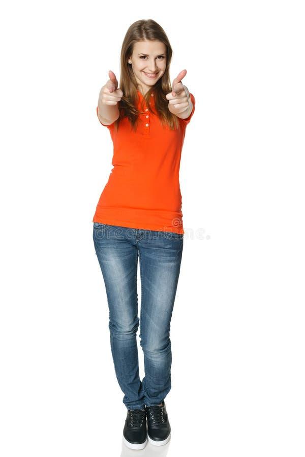 Lycklig kvinna som pekar på dig som står oavkortad längd arkivfoto