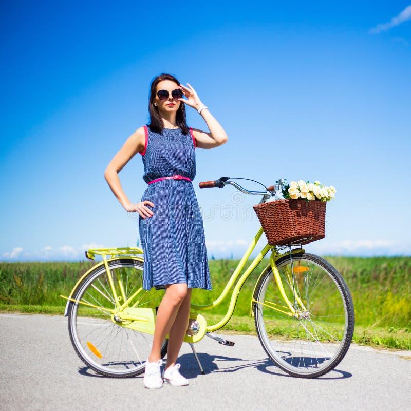 Lycklig kvinna som poserar med den retro cykeln på vägen arkivbilder