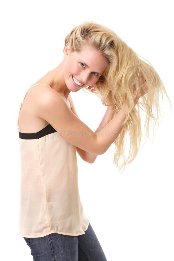 Lycklig kvinna som poserar med händer i hår royaltyfria bilder
