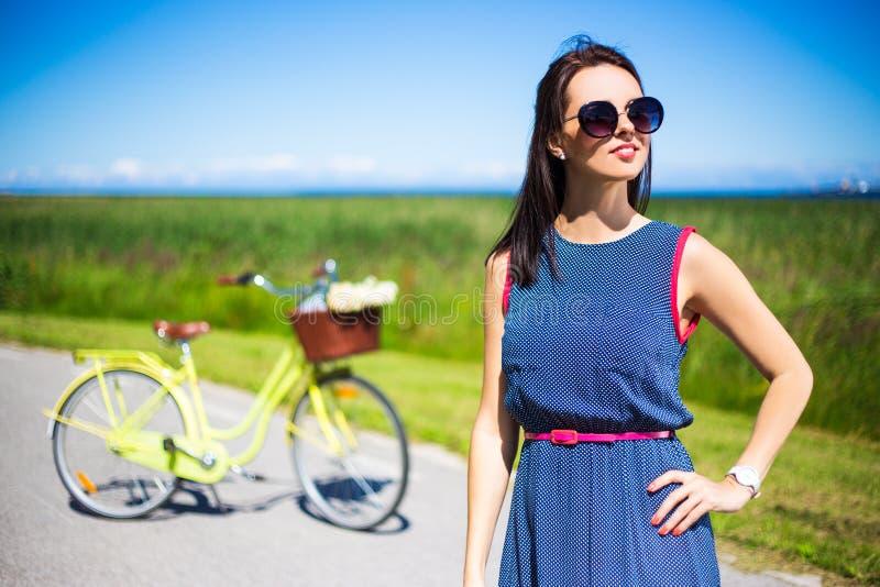 Lycklig kvinna som poserar på vägen med den retro cykeln royaltyfri fotografi