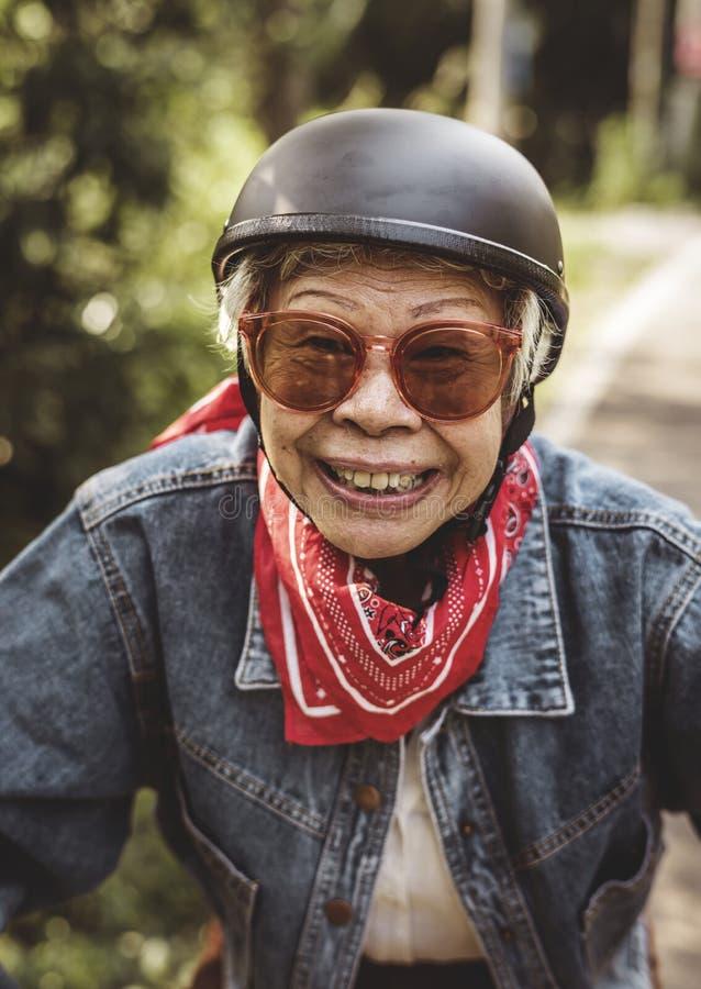Lycklig kvinna som rider en klassisk sparkcykel arkivfoto