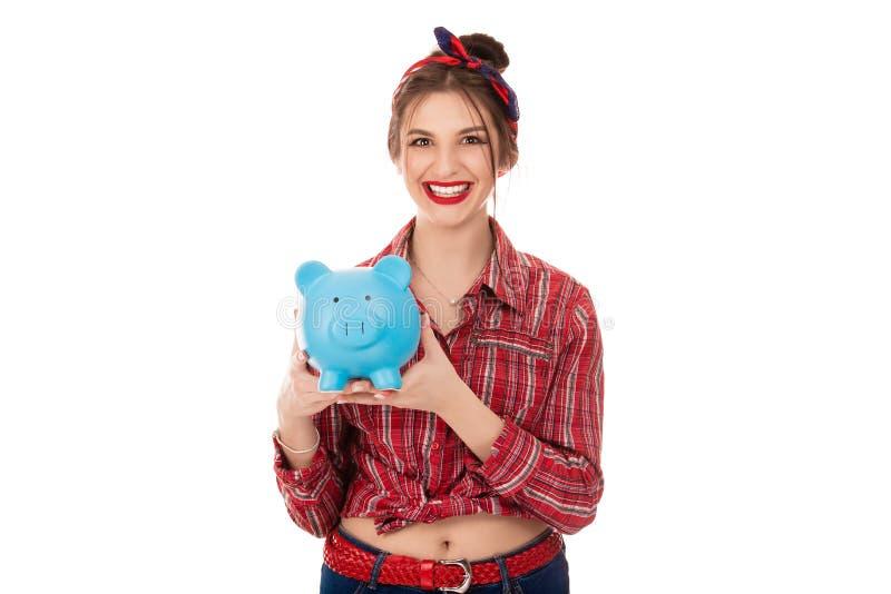 Lycklig kvinna som rymmer den blåa spargrisen med massor av pengar royaltyfri fotografi