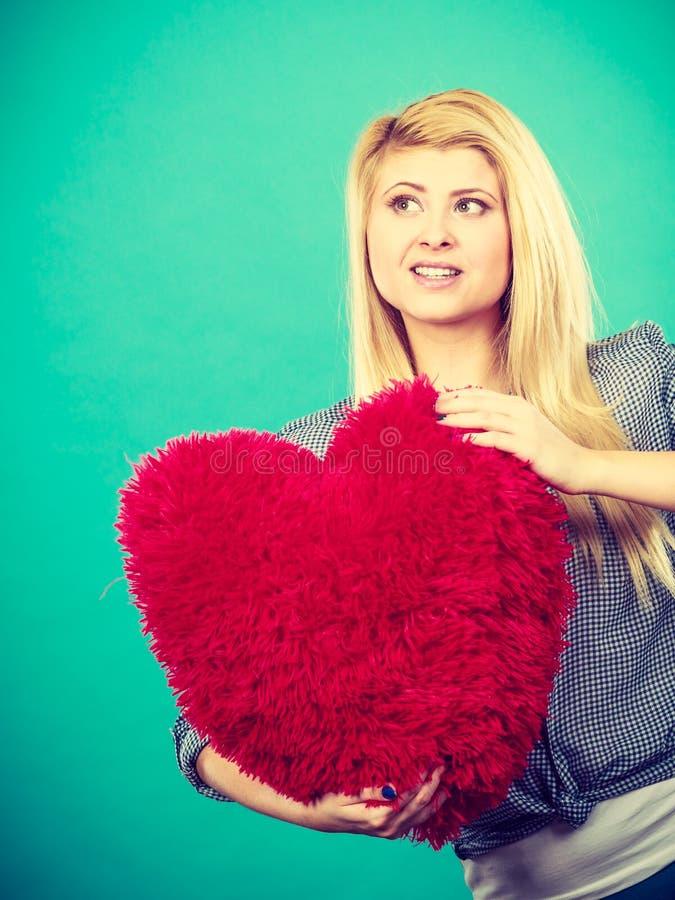 Lycklig kvinna som rymmer den röda kudden i hjärtaform arkivfoton