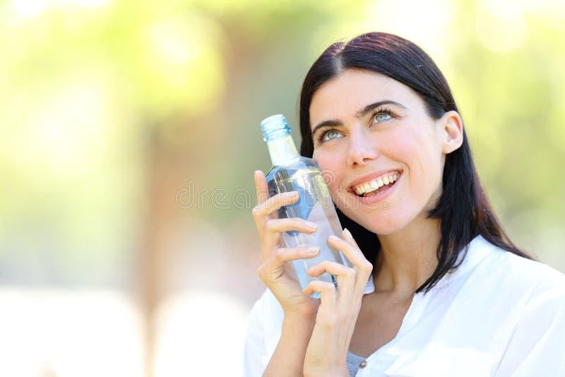Lycklig kvinna som rymmer en flaska av vatten royaltyfri bild