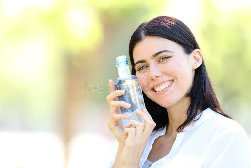 Lycklig kvinna som rymmer en flaska av vatten som ser dig royaltyfria bilder