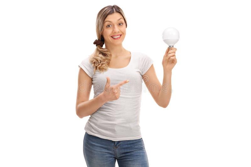 Lycklig kvinna som rymmer en LETT ljus kula och peka royaltyfria foton