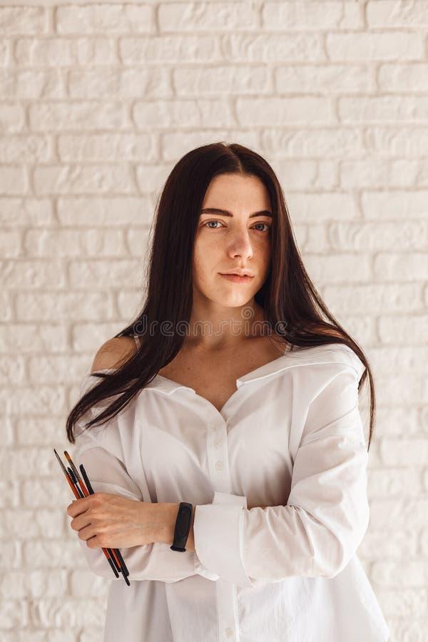 Lycklig kvinna som rymmer en makeupborste fotografering för bildbyråer