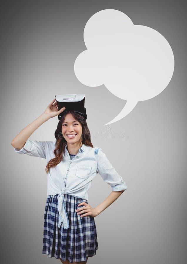 Lycklig kvinna som rymmer en VR-hörlurar med mikrofon med anförandebubblan mot grå bakgrund royaltyfria foton