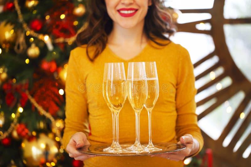 Lycklig kvinna som rymmer exponeringsglas av champagne på silvermagasinet arkivfoton