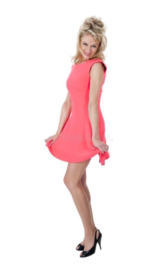 Lycklig kvinna som rymmer hennes klänning arkivbild