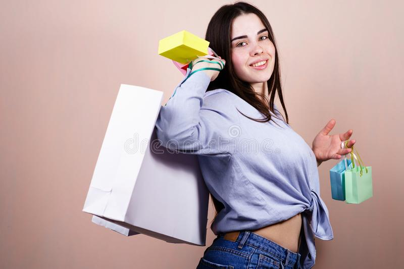 Lycklig kvinna som rymmer många shoppa påsar med gods royaltyfri fotografi